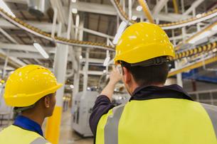 Workers discussing printing press conveyor belts overheadの写真素材 [FYI02697313]