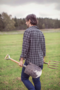 Rear view of man with gardening tools walking on organic farmの写真素材 [FYI02697319]