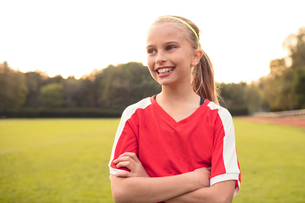 Happy female athlete looking away standing with arms crossed on soccer fieldの写真素材 [FYI02697328]