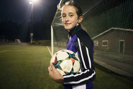 Portrait of girl with soccer ball standing against goal postの写真素材 [FYI02697405]