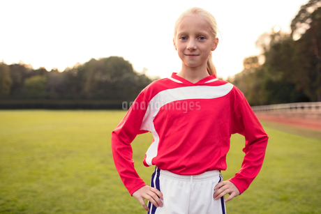 Portrait of confident girl standing with hands on hip at soccer fieldの写真素材 [FYI02697432]