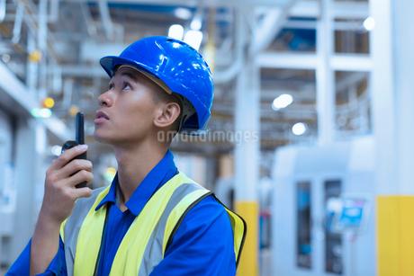 Worker in hard-hat using walkie-talkie in factoryの写真素材 [FYI02697501]