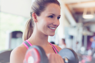 Close up smiling woman doing dumbbell biceps curls at gymの写真素材 [FYI02697511]