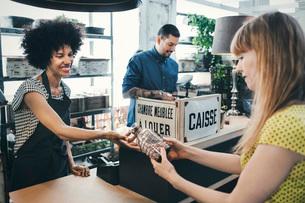 Happy worker giving glass vase to customer in storeの写真素材 [FYI02697515]