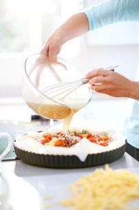 Woman preparing tomato quiche in kitchenの写真素材 [FYI02697572]