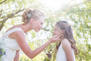Bride and bridesmaid facing each other in domestic garden during wedding receptionの写真素材 [FYI02697577]