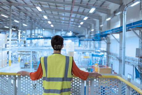 Worker in reflective clothing on platform looking out over factoryの写真素材 [FYI02697579]