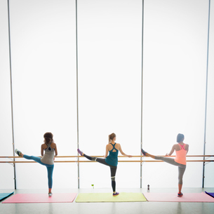 Women stretching legs at barre in exercise class gym studioの写真素材 [FYI02697592]