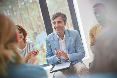 Smiling man clapping in group therapy sessionの写真素材 [FYI02697614]