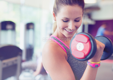 Close up smiling woman doing dumbbell biceps curls at gymの写真素材 [FYI02697629]