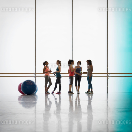 Women talking and drinking water at barre in exercise class gym studioの写真素材 [FYI02697649]