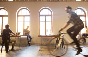 Casual businessman riding bicycle in open officeの写真素材 [FYI02697655]