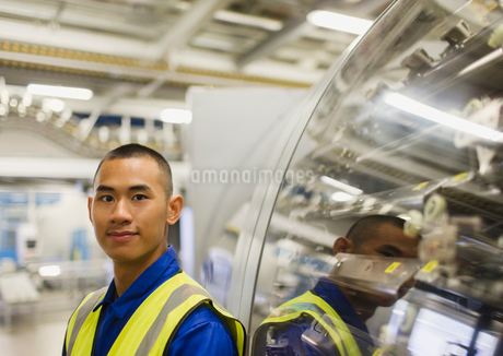 Portrait confident worker leaning on machinery in factoryの写真素材 [FYI02697688]