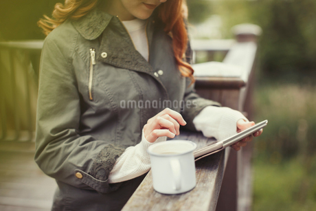 Woman drinking coffee using digital tablet at balcony railingの写真素材 [FYI02697710]