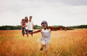 Playful boy with wings in aviator's cap and flying goggles in fieldの写真素材 [FYI02697751]