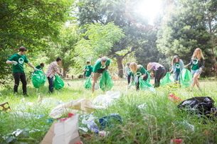 Environmentalist volunteers picking up trash in fieldの写真素材 [FYI02697752]