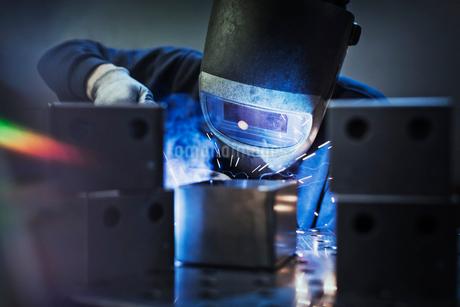 Welder using welding torch on part in steel factoryの写真素材 [FYI02697773]