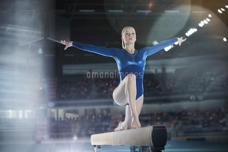 Focused female gymnast performing on balance beam in arenaの写真素材 [FYI02697804]