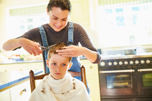 Unhappy boy getting haircut from mother in kitchenの写真素材 [FYI02697817]