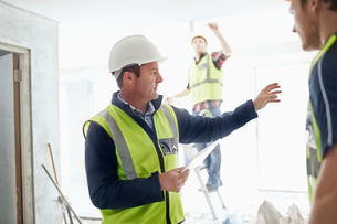Foreman with digital tablet gesturing to construction worker at construction siteの写真素材 [FYI02697832]