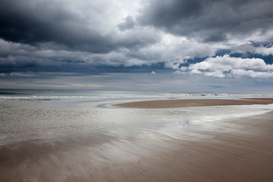 Clouds over beach at low tideの写真素材 [FYI02697835]