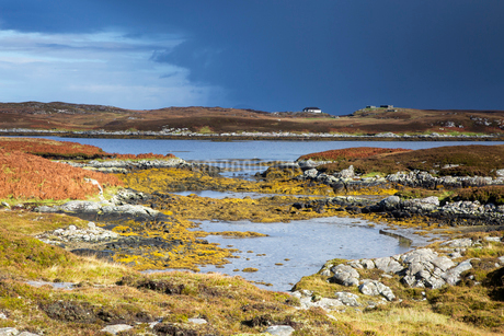 Sunny tranquil view craggy rocks and lake, Loch Euphoirt, North Uist, Outer Hebridesの写真素材 [FYI02697865]