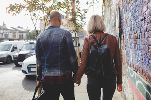 Rear view of couple holding hands while walking on sidewalk in cityの写真素材 [FYI02697914]
