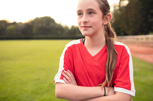 Girl standing with arms crossed on soccer fieldの写真素材 [FYI02697937]