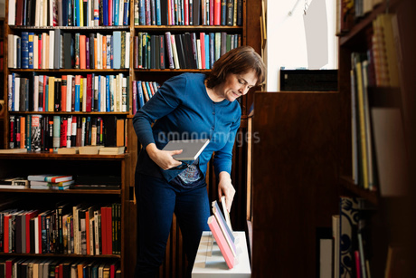 Librarian arranging books for display in antique shopの写真素材 [FYI02697966]