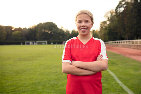 Portrait of happy female soccer player standing with arms crossed on fieldの写真素材 [FYI02697979]