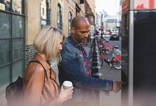 Couple operating bike vending machine on sidewalk in cityの写真素材 [FYI02697983]