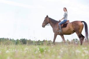 Woman horseback riding in rural fieldの写真素材 [FYI02698020]