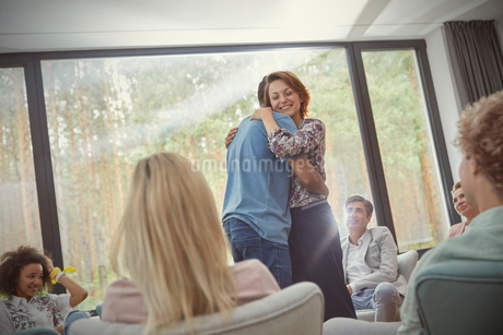 Man and woman hugging in group therapy sessionの写真素材 [FYI02698027]