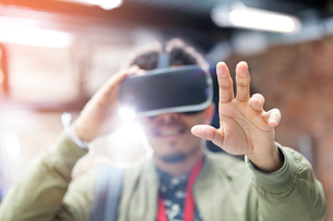 Portrait man trying virtual reality simulator glasses reachingの写真素材 [FYI02698065]
