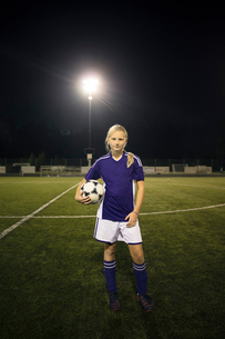 Portrait of confident girl standing holding ball on soccer field against sky at nightの写真素材 [FYI02698112]