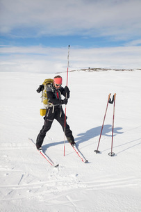 Full length of mature female skier inserting pole in snowの写真素材 [FYI02698123]