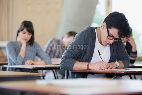 Focused male college student taking test at desk in classroomの写真素材 [FYI02698137]