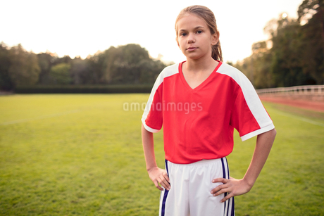 Portrait of confident female soccer player standing with hands on hip at fieldの写真素材 [FYI02698151]