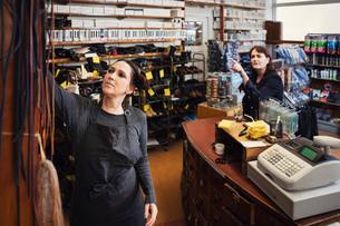 Shoemaker assisting female customer at repair storeの写真素材 [FYI02698187]