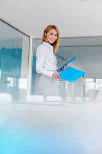 Portrait smiling businesswoman placing folders on conference tableの写真素材 [FYI02698189]