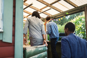 Rear view of male friends entering log cabin during summer partyの写真素材 [FYI02698323]