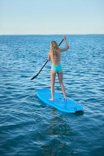 Young woman in bikini paddleboarding in summer oceanの写真素材 [FYI02698326]