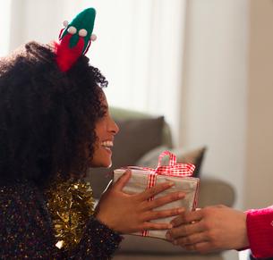 Enthusiastic girlfriend receiving Christmas gift from boyfriendの写真素材 [FYI02698341]