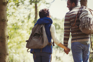 Couple with backpacks holding hands hiking in woodsの写真素材 [FYI02698348]