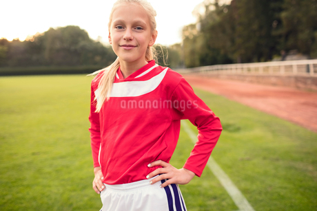 Portrait of confident girl standing with hands on hip at soccer fieldの写真素材 [FYI02698351]