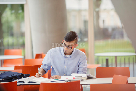 Male college student studying at tableの写真素材 [FYI02698385]