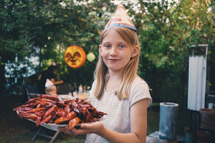 Portrait of girl holding plate with cooked crayfish at garden dinner partyの写真素材 [FYI02698406]