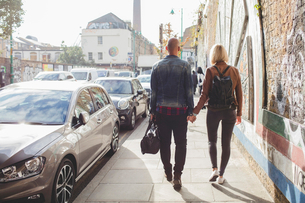Full length rear view of couple holding hands while walking on sidewalk by traffic in cityの写真素材 [FYI02698413]