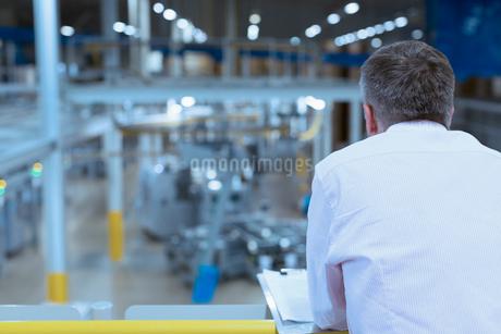 Supervisor with clipboard on platform overlooking factoryの写真素材 [FYI02698535]