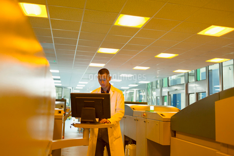 Worker in lab coat at computer among printers in printing plantの写真素材 [FYI02698562]